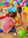 Children building blocks in kindergarten. Group kids playing toy floor . Stock Images