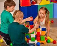 Children building blocks in kindergarten. Group kids playing toy floor. Royalty Free Stock Image