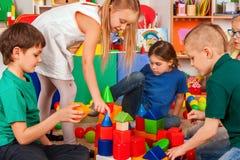 Children building blocks in kindergarten. Group kids playing toy floor. Stock Images