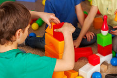 Children building blocks in kindergarten. Group kids playing toy floor . Children building blocks in kindergarten. Group kids playing toy on floor. Top view of royalty free stock images