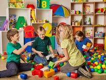 Children building blocks in kindergarten. Group kids playing toy floor . Royalty Free Stock Photo
