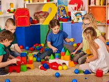 Children building blocks in kindergarten. Group kids playing toy floor . Royalty Free Stock Images