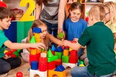 Children building blocks in kindergarten. Group kids playing toy floor . Children building blocks in kindergarten. Group kids playing toy on floor. Top view of royalty free stock images