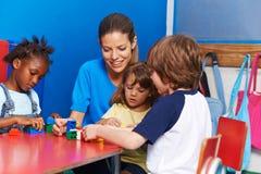 Children building with blocks in kindergarten. Children and nursery teacher building with blocks in kindergarten Royalty Free Stock Photo