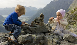 Children building a cairn. Little boy and girl making a cairn together. Aandalsnes, Rauma, Norway in the background stock images