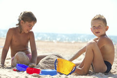 Children building sand castle on beach Stock Images