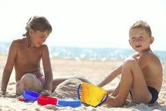 Children building sand castle on beach Stock Images