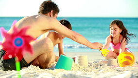 Children building sand castles with their father stock video footage