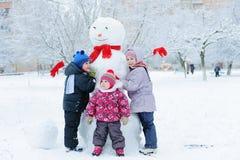 Children building snowman in garden Royalty Free Stock Image