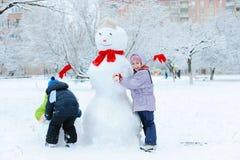 Children building snowman in garden Stock Image