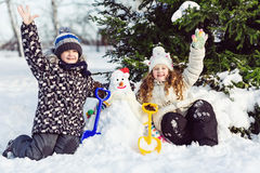 Children building snowman in the park. Royalty Free Stock Image