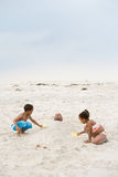 Children burying father in sand Royalty Free Stock Image