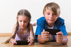Children burying in mobile phones. Little girl and teenage boy burying in mobile phones laying on the floor at home royalty free stock photos