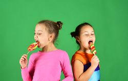 Children with busy faces pose with candies on green background. Sisters with round and long shaped lollipops. Happiness and dessert concept. Girls eat big stock images