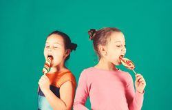 Children with busy faces pose with candies on green background. Sisters with round and long shaped lollipops. Happiness and dessert concept. Girls eat big royalty free stock image