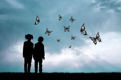 Children and butterflies at sunset Stock Image