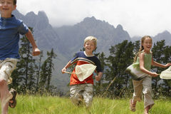 Children With Butterfly Nets Running Through Field Stock Image
