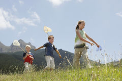 Children With Butterfly Nets Walking Through Field Royalty Free Stock Photo