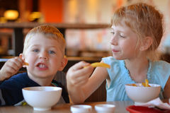 Children in cafe eat potato Stock Image