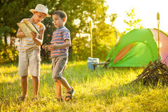 Children on a camping trip learning how to read and use a map. Camp in the tent - two brothers on the camping stock photo