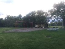 Children& x27; campo da giuoco di s al crepuscolo con le oscillazioni, lo scorrevole, l'erba e la tavola di picnic Immagine Stock