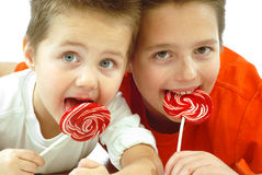 Children with candy. Two cute little brothers enjoying candy together; isolated on white royalty free stock photo