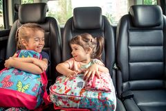 Children in the car go to school, happy, sweet faces of sisters stock photos