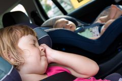 Children in a car seats stock photography