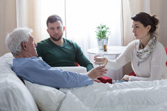 Children caring about ill father. Children caring about terminally ill cancer father stock photography