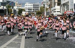 Children in carnival costumes running along a street royalty free stock images
