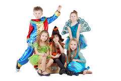 Children in carnival costumes sit on chest. And stand beside Royalty Free Stock Photo