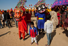 Children in carnival crowd with scary evil characters Royalty Free Stock Image
