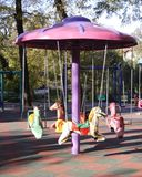 Children carousel. Pink children carousel waiting for kids in a sunny autumn afternoon Royalty Free Stock Images