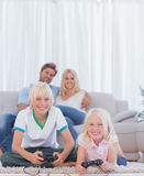 Children on the carpet playing video games. In the living room royalty free stock photography