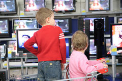 Children in carriage for purchases look at TVs in royalty free stock photography