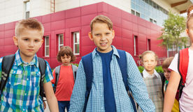 Children carry rucksacks and walk near school Royalty Free Stock Image