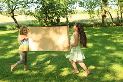 Children carrying a box. Barefoot children - two smiling girls carrying a paper box stock photo