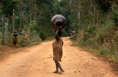 Children carrying pots on their heads in Burundi. Royalty Free Stock Image