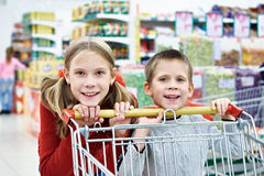 Children with cart shopping Royalty Free Stock Photos