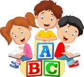 Children cartoon reading book and sitting on alphabet blocks Stock Photos