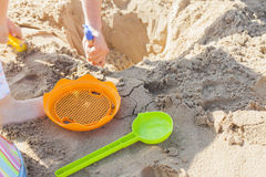Children carving a hole in the beach sand. Royalty Free Stock Photography