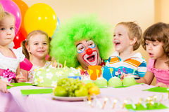 Children celebrating birthday party with clown Royalty Free Stock Image