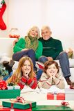 Children celebrating christmas at grandparents. Two children celebrating christmas at their grandparents with gifts stock photo