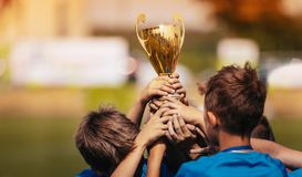 Children Celebrating Sport Success Outdoor. Boys Holding Golden Cup. Sport Tournament for Children royalty free stock image