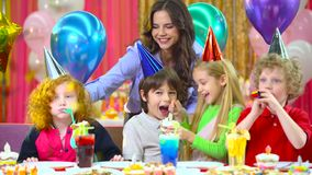 Children celebrating their birthday with mother and fiends at cafe. Children in colorful hats celebrating their birthday with mother and fiends at cafe. They stock video footage