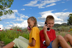 Children on cell phones. Children sitting on grass outside, talking on cell phones Stock Photography