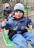 Children on chain swing Stock Photo