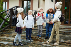 Children Chatting on School Stairs. Group of children chatting standing on schools doorstep, all wearing backpacks and similar knit clothes stock image