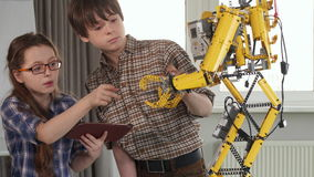 Children check the toy robot. Two children checking the toy robot on the table. Pretty girl in glasses holding tablet in her hands. Little brunette boy pointing stock footage
