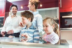 Children checking out the new kitchen their parents are about to buy. Dialing knobs of the oven stock photos